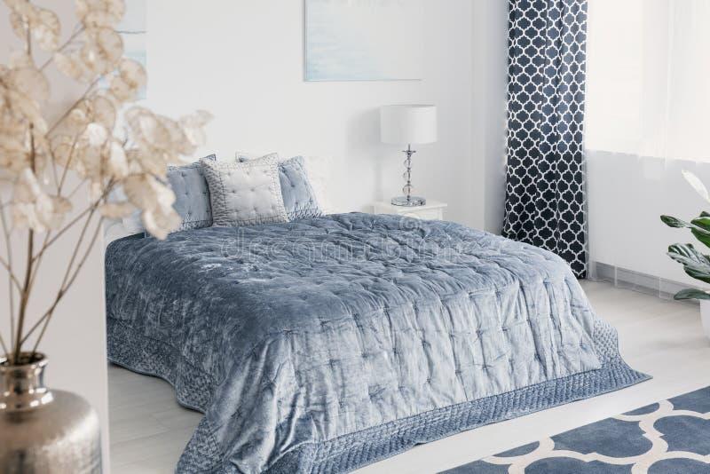 Blumen im weißen eleganten Schlafzimmer, das mit blauen Blättern auf Bett nahe bei Lampe Innen ist und drapiert Reales Foto lizenzfreie stockfotografie