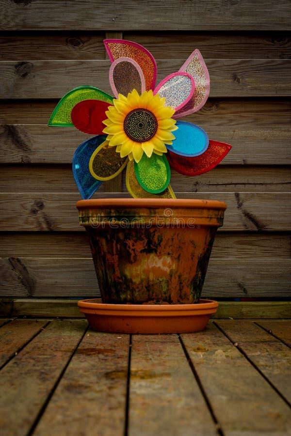 Blumen-Topf mit einer Spielzeugwindmühle und einer Sonnenblume stockfotografie