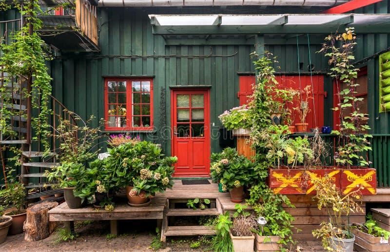 Blumen und Anlage des traditionellen Dorfhauses von Christiania Freetown mit Gartenzubehör und -fahrrad stockbilder