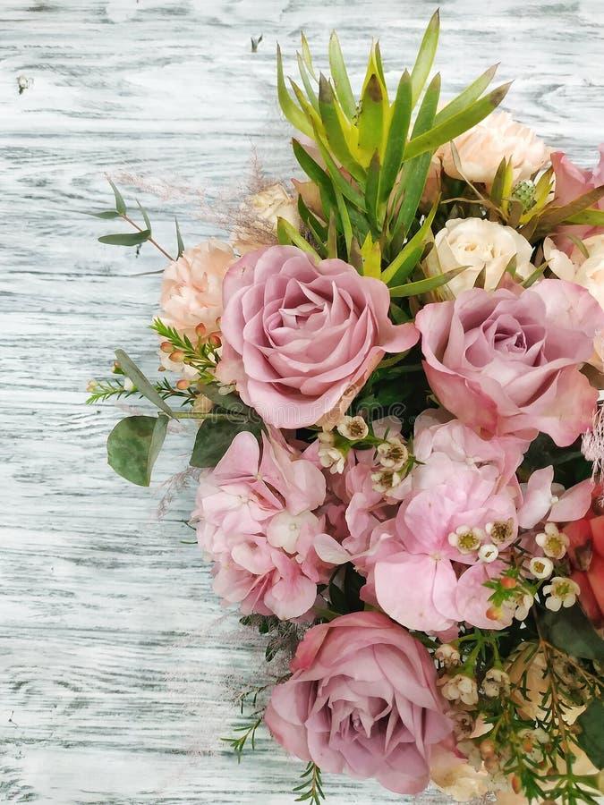 Blumen und Anlagen auf einem weißen hölzernen Hintergrund lizenzfreies stockbild