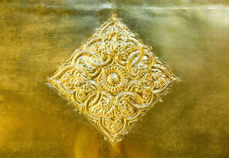 Blumen- und Blattmuster in thailändischer Lanna-Art, die auf Goldmetallplattenhintergrund geschnitzt wird, verzieren auf goldener stockfoto