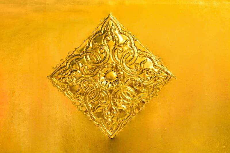 Blumen- und Blattmuster in thailändischer Lanna-Art, die auf Goldmetallplattenhintergrund geschnitzt wird, verzieren auf goldener stockfotografie