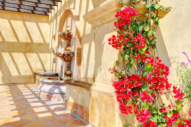 Blumen und Brunnen auf spanischen Wanddetails. stockbilder