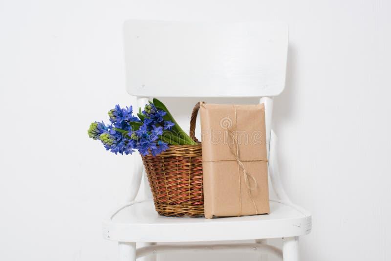Blumen und eingewickeltes Geschenk stockfotos