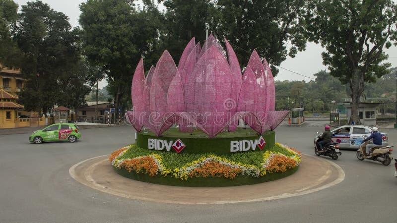 Blumen und hellpurpurne geometrische Installation der Zusammenfassung in einem Kreisverkehr in Hanoi, Vietnam lizenzfreie stockbilder