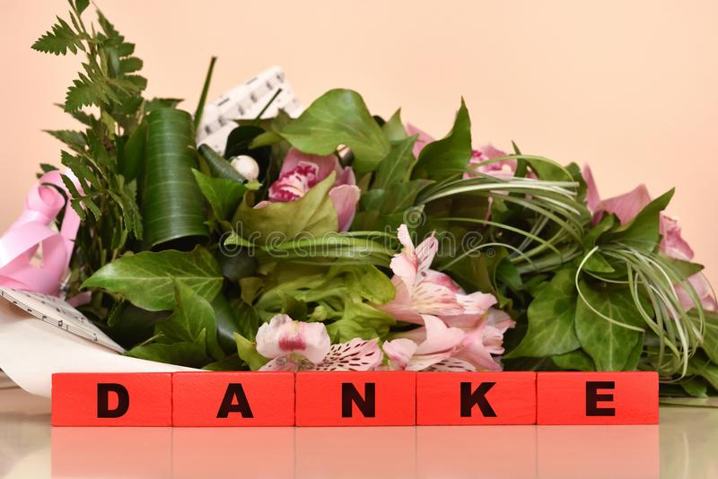 Blumen und rote Holzklötze mit Danke-Mitteilung stockfotos