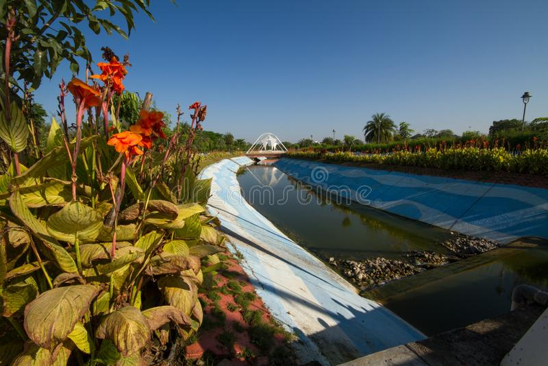 Blumenanlagen und -bäume nahe durch Kanal mit blauem Himmel stockfotografie