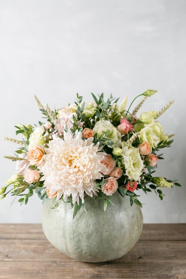 Blumenanordnung im Kürbis auf dem Tisch von hölzernen Planken lizenzfreie stockfotos