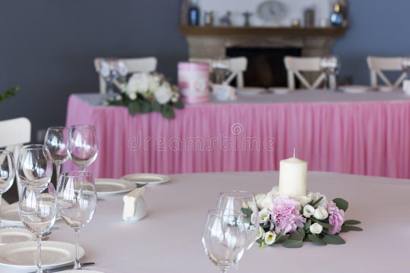 Blumenanordnung im Rosa mit weißen Kerzen auf der festlichen Tabelle am Hochzeitstag stockfoto