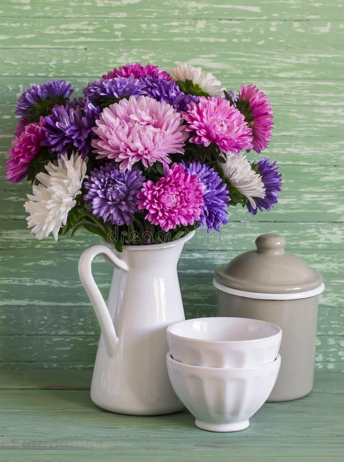Blumenastern in einem Weiß emaillierten Pitcher und Weinlesetonware - keramische Schüssel und emailliertes Glas, auf einem blauen stockbild