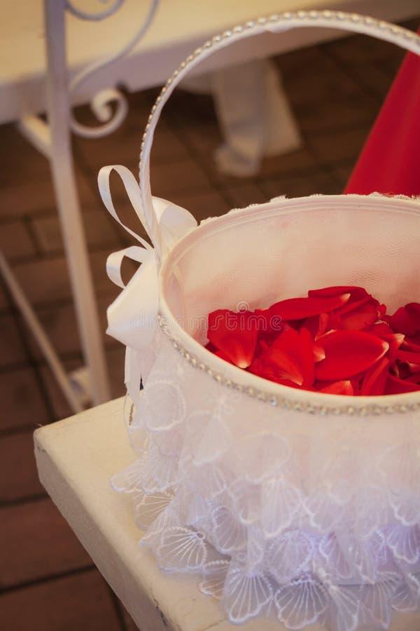 Blumenblätter von roten Rosen in einem Heiratskorb stockfoto