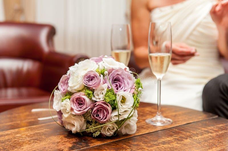 Blumenblumenstrauß- und -champagnergläser auf hölzerner Tabelle stockfoto