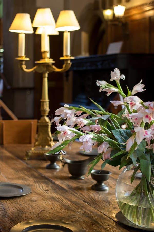 Blumendekoration auf eichenem Tisch Feines Speisen des High Society-Zeitraums stockbilder