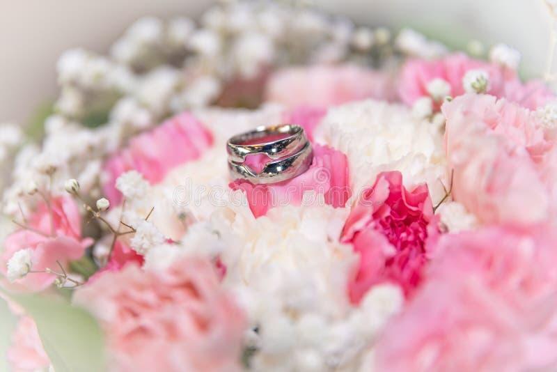 Blumendekoration an der Hochzeit Hochzeitsblumenstrauß der Braut und des Zeuges Goldene Eheringe auf den Blumen lizenzfreies stockbild