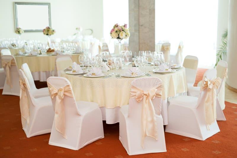 Blumendekoration der schönen Hochzeit auf einer Tabelle in einem Restaurant Weiße Tischdecken, heller Raum stockbilder