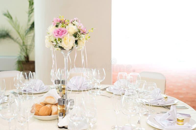 Blumendekoration der schönen Hochzeit auf einer Tabelle in einem Restaurant Weiße Tischdecken, heller Raum lizenzfreie stockfotos