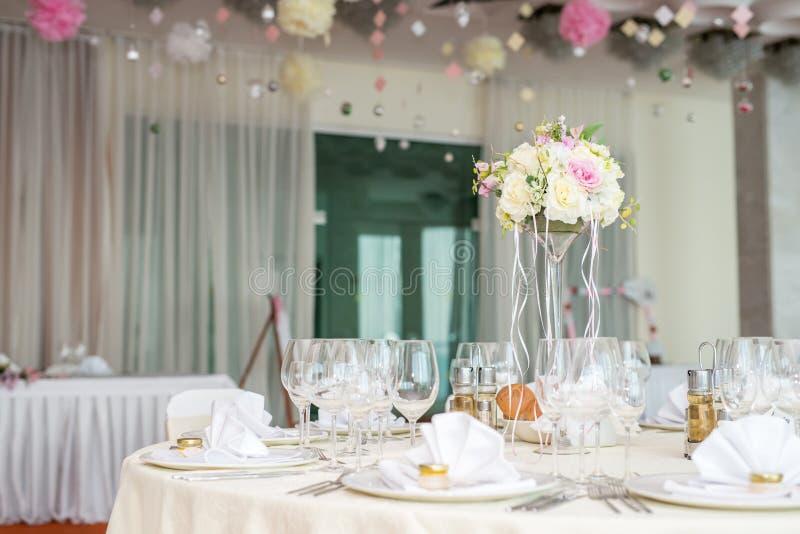 Blumendekoration der schönen Hochzeit auf einer Tabelle in einem Restaurant Weiße Tischdecken, heller Raum lizenzfreies stockbild