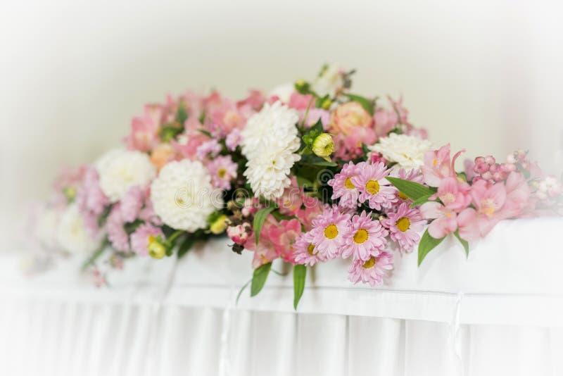 Blumendekoration der schönen Hochzeit auf einer Tabelle in einem Restaurant Weiße Tischdecken, heller Raum stockfotos