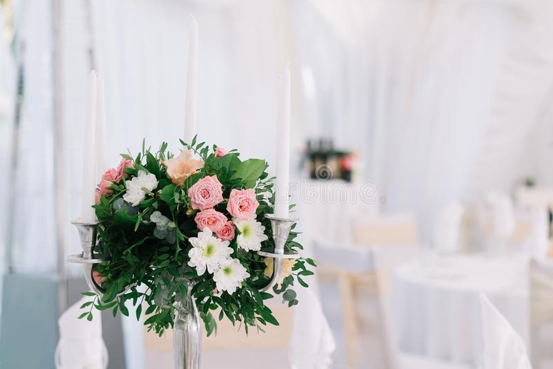 Blumendekoration der schönen Hochzeit auf einer Tabelle in einem Restaurant Weiße Tischdecken, heller Raum, Kerzen, Nahaufnahmesc stockfotografie