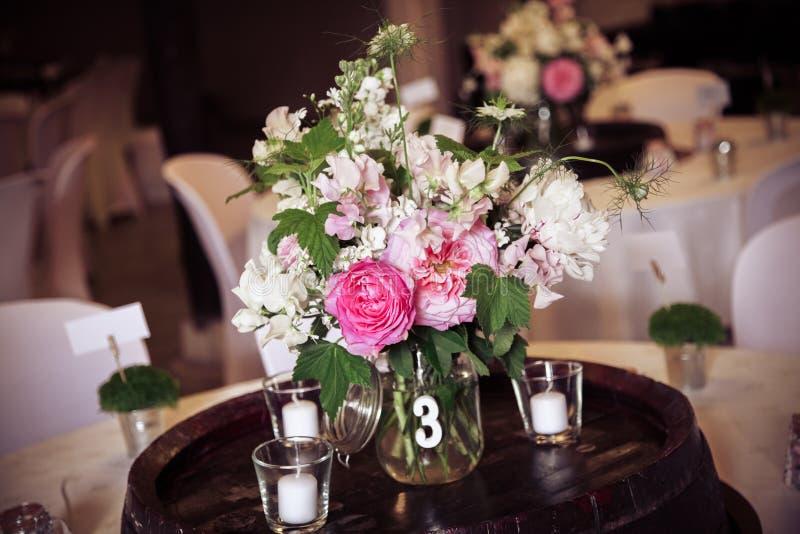 Blumendekoration mit rosa Rosen auf einer Hochzeitsempfangtabelle stockbild