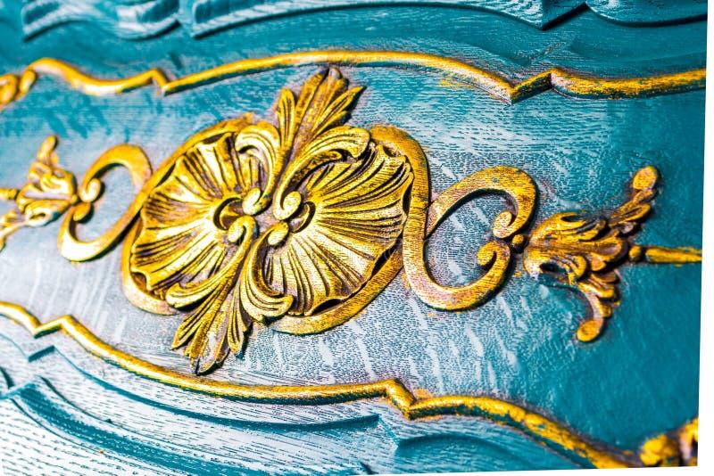 Blumendetails über einen hölzernen Kasten, antike Art Schließen Sie oben von den gelben Carvings auf schön gemeißeltem blauem Möb stockfoto
