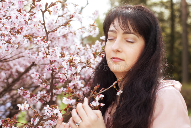 Blumengarten der Brunettefrau im Frühjahr stockbild