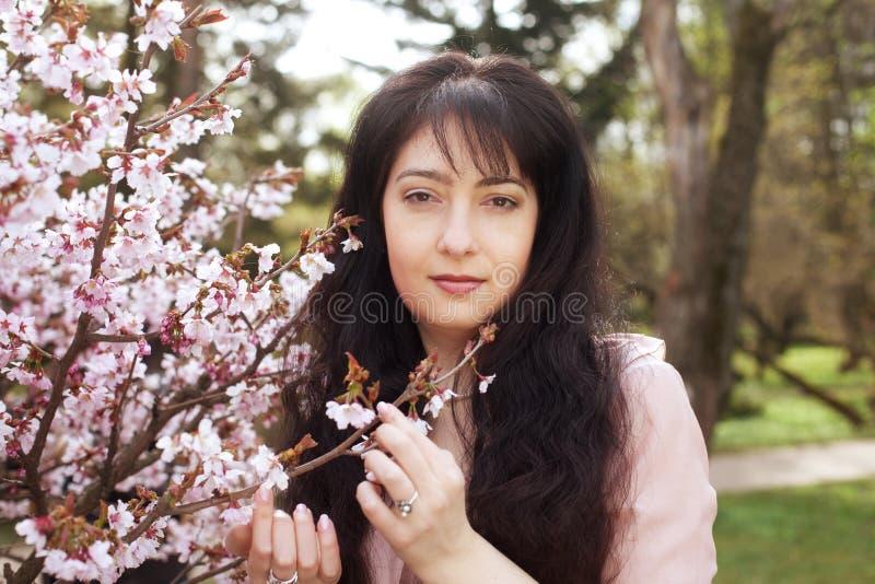 Blumengarten der Brunettefrau im Frühjahr lizenzfreie stockbilder