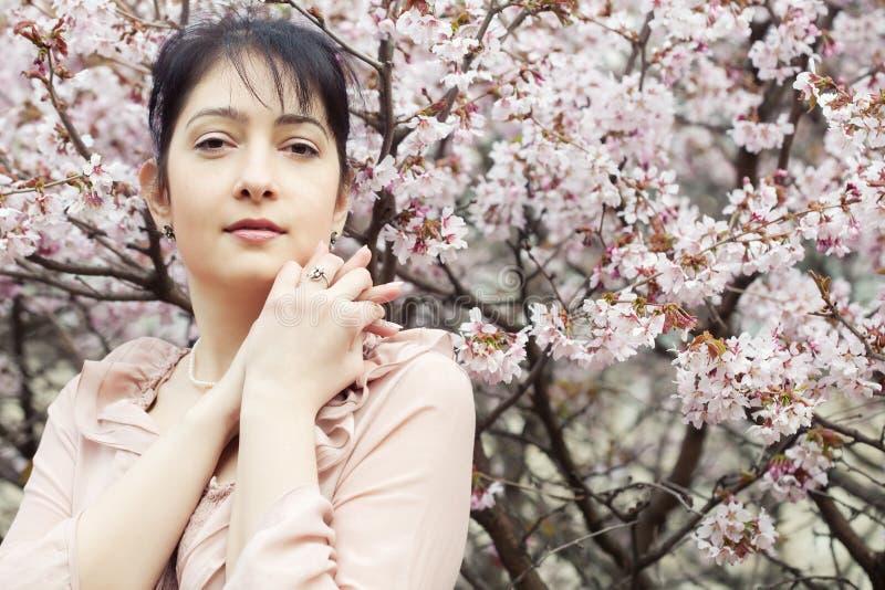 Blumengarten der Brunettefrau im Frühjahr lizenzfreies stockfoto