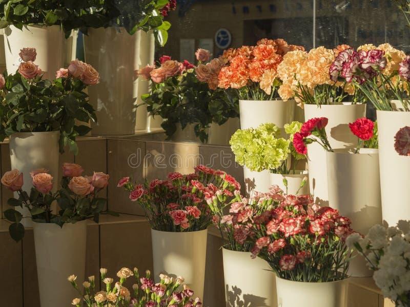 Blumengeschäft planty von den rosa Rosen und rotes gelb-orangees und gree stockbilder