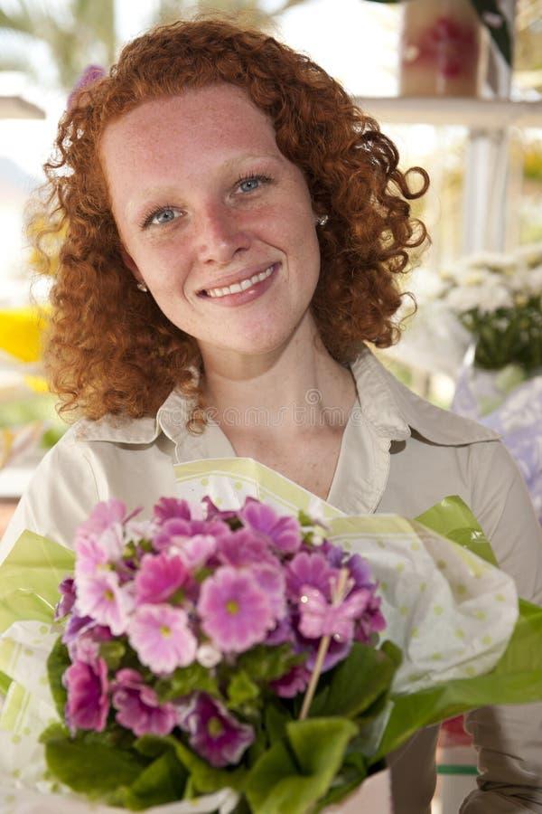 Blumengeschenk: Frau, die einen Blumenstrauß gibt lizenzfreie stockfotos