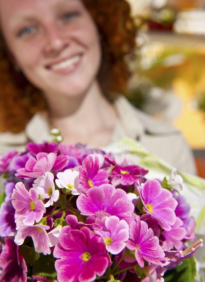Blumengeschenk: Frau, die einen Blumenstrauß gibt lizenzfreies stockbild