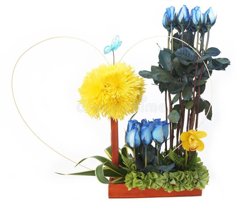 Blumengeschenkvorkehrung getroffen mit blauen Rosen mit langen Stämmen und gelben Blumen innerhalb eines hölzernen Topfes stockbild