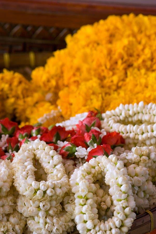Blumengirlanden am Tempel in Thailand lizenzfreie stockfotos
