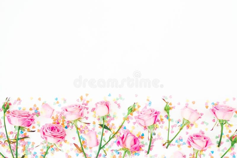 Blumengrenzrahmen mit rosa Blumen und helle Süßigkeitskonfettis auf weißem Hintergrund Flache Lage, Draufsicht Rosenblumenbeschaf stockfoto