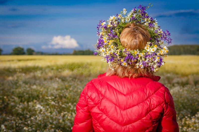 Blumenkranz im Kopf auf unscharfem Landschaftshintergrund stockfotografie
