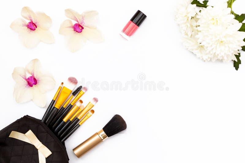 Blumenorchidee und -chrysantheme, Make-upbürsten und Nagellack auf weißem Hintergrund Minimales Schönheitskonzept Flache Lage lizenzfreie stockfotografie