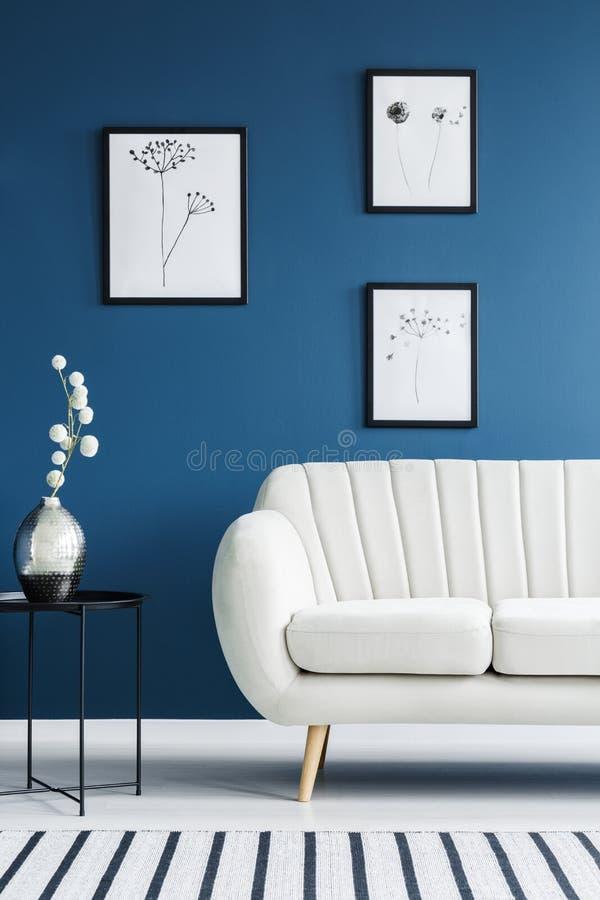 Blumenposter und Sofa lizenzfreie stockfotos