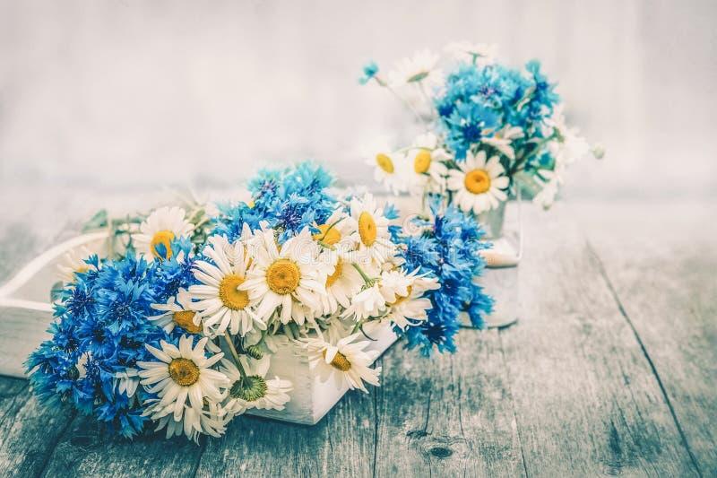 Blumenstr?u?e von sch?nen wilden Blumen von G?nsebl?mchen und von Kornblumen auf einem h?lzernen alten Hintergrund lizenzfreie stockfotos