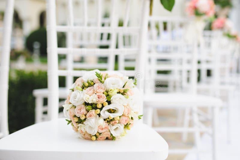 Blumenstrauß auf weißem Stuhl lizenzfreie stockbilder