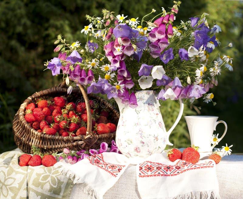 Blumenstrauß Blumen noch des Lebens mit Erdbeeren lizenzfreie stockbilder