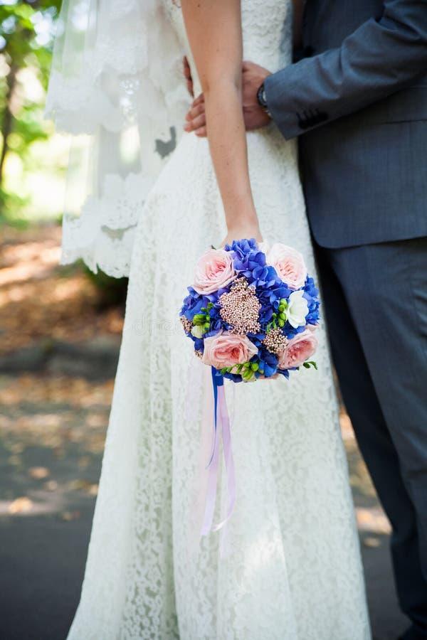 Blumenstrauß in den Händen der Braut und des Bräutigams lizenzfreies stockfoto