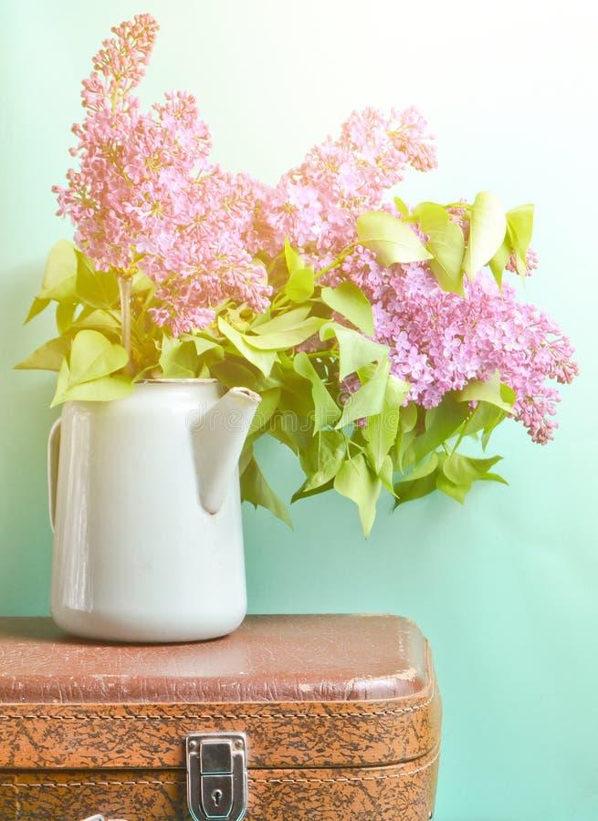 Blumenstrauß der Flieder in einer alten emaillierten Teekanne auf Weinlesekoffer auf blauem Hintergrund Retrostilstillleben stockbilder