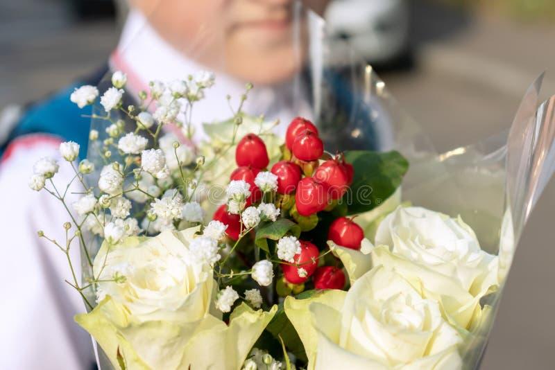 Blumenstrauß der Nahaufnahme der weißen Rosen und des unscharfen Jungen im Hintergrund stockfoto