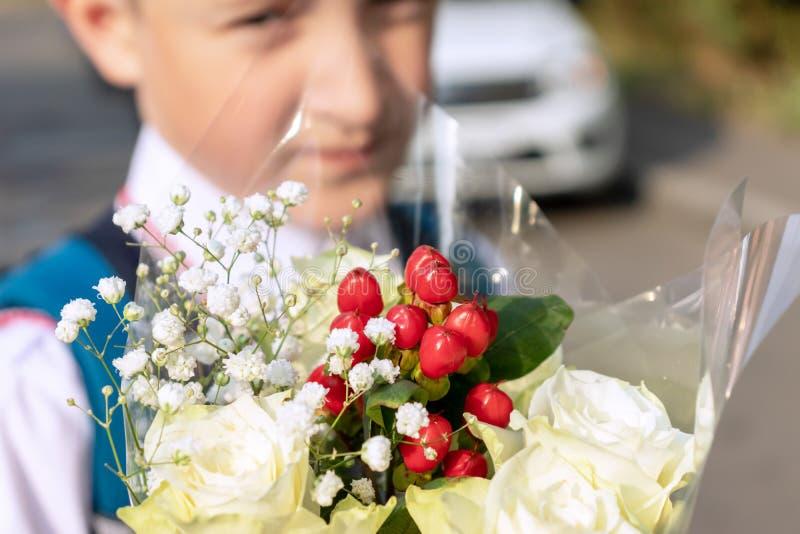 Blumenstrauß der Nahaufnahme der weißen Rosen und des unscharfen Jungen im Hintergrund lizenzfreie stockbilder