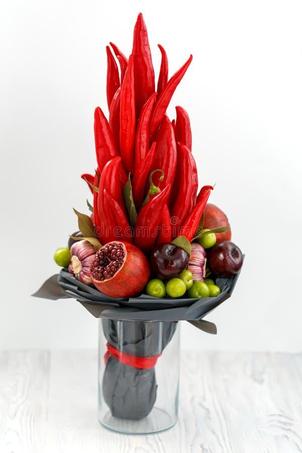 Blumenstrauß, der rotem Pfeffer, Granatäpfeln, blauen Pflaumen, Lorbeerblättern und aus rosafarbenen Blumen als Satz für die Vorb stockfotografie
