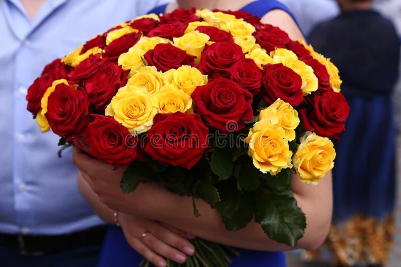 Blumenstrauß der roten und gelben Rosen in den Händen stockbilder