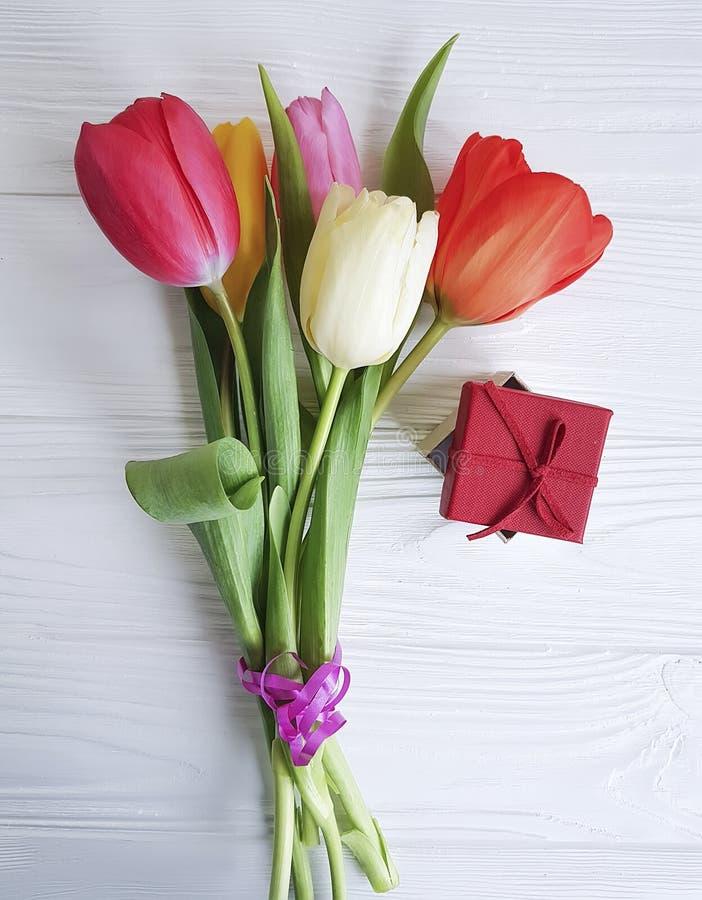 Blumenstrauß der Tulpenschönheit auf einem weißen hölzernen Hintergrund, Geschenkbox stockfotografie