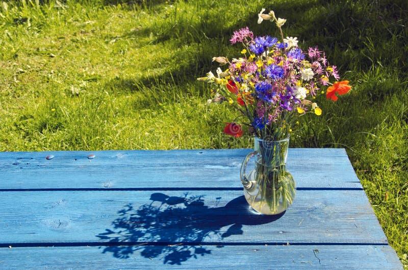 Blumenstrauß der wilden Blumen des Sommers im Glasvase auf blauer Tabelle stockfoto