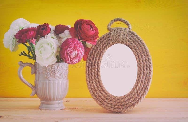 Blumenstrauß des Frühlinges blüht nahe bei leerem Weinlesefotorahmen lizenzfreies stockbild