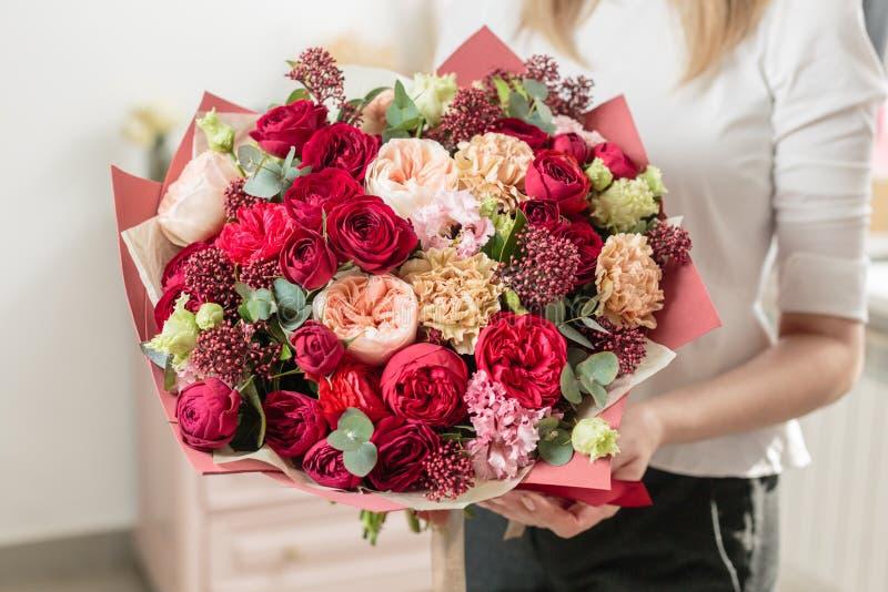 Blumenstrauß in hohem Grade des Rotes gefärbt schönes Luxusbündel Mischblumen in der Hand der Frau die Arbeit des Floristen an a stockbilder